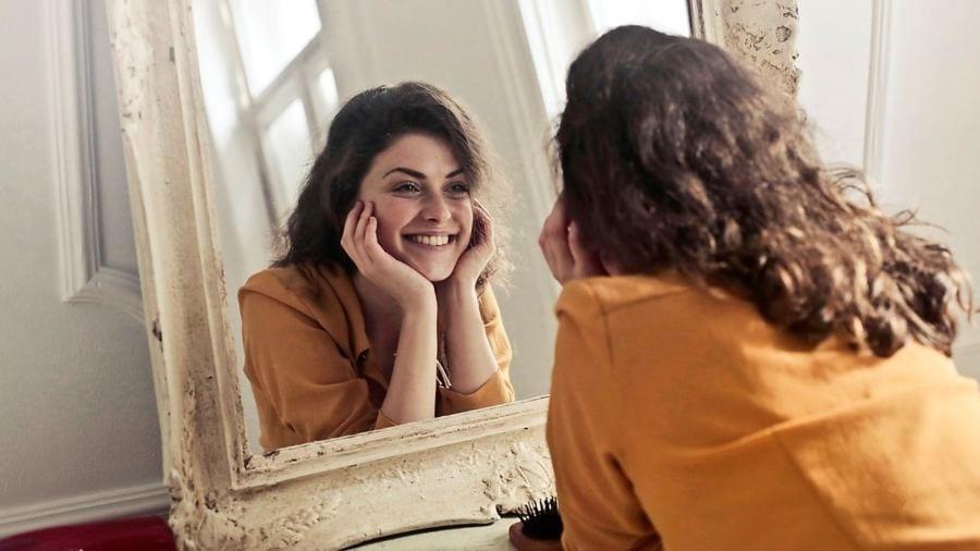 mulher se olha no espelho e sorri